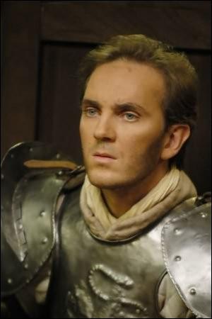 Dans l'épisode où Arthur apprend que la dame du lac va lui envoyer une porte interdimensionnelle, il est accompagné par Bohort et Lancelot. Où se trouve Lancelot par rapport à Arthur à ce moment-là ?