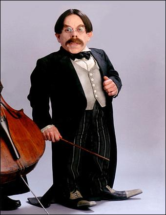 Quel est le nom de ce professeur, qui enseigne la lévitation et qui dirige l'orchestre et la chorale de Poudlard ? Dans le premier épisode, il n'a pas la même apparence.