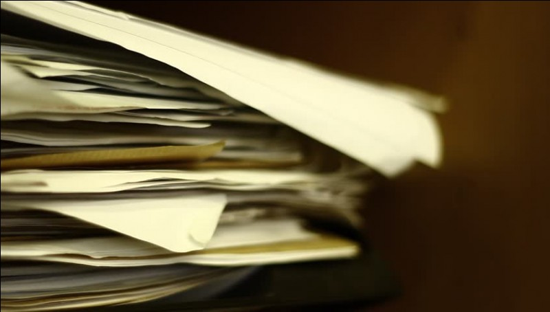 Mrs Dock had her secretary ....... a pile of documents.