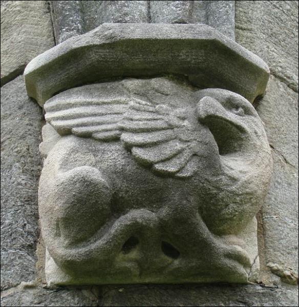 Quadrupède avec un corps de lion, il possède quatre pattes armés de griffes et couvertes d'écailles, une tête au bec crochu, une queue de saurien, des ailes et des serres d'aigle.