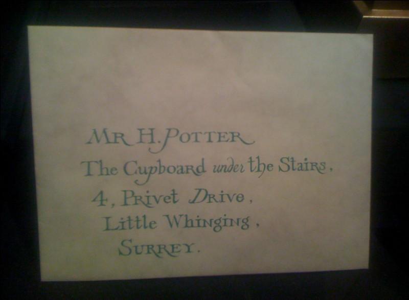 Comment arrive la première lettre destinée à Harry, et qui dit qu'il est admis au collège Poudlard ?