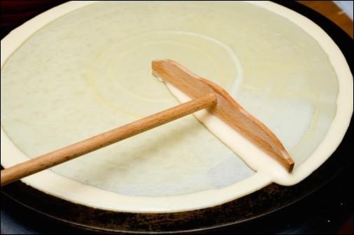 Et voici la star de notre région : la crêpe ! Ce délicieux dessert est un mélange de lait, d'oeufs, de farine et de sucre. Mais sur cette photo nous voyons un objet étrange sous la crêpe... Quel est le nom de cet appareil ?