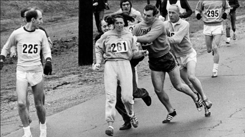 Sur la photo, vous pourrez voir la journaliste Kathrine Switzer en train de courir le marathon de Boston en 1967 ! Elle porte le numéro 261.Mais, que peut bien faire le type derrière elle et dont on voit difficilement la tête et pourquoi ?