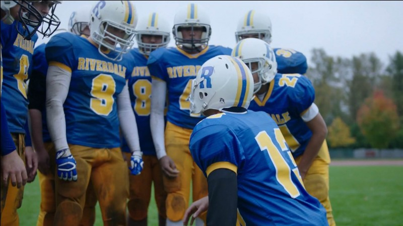 Quelle lettre apparaît sur les vestes bleues de l'équipe de foot ?