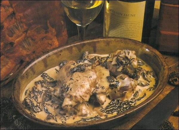 Avec quoi cuisine-t-on le coq dans un plat traditionnel du Jura ?