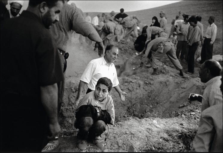 Ce garçon tient le pantalon de son père prêt à être enterré dans ses bras, de quoi celui-ci est-il décédé ?