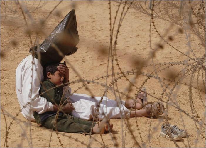 Quelle est la nationalité de ce père et de son enfant dans un centre de détention pour prisonniers de guerre à l'intérieur d'un camp de base état-unien ?