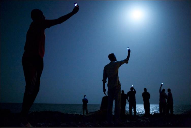 Pourquoi ces immigrants africains lèvent-ils leur téléphone vers le ciel à Djibouti ?