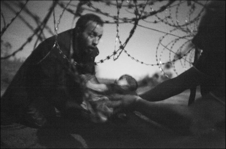 À qui cet individu tend-il ce bébé à travers un trou de fils barbelés afin de franchir la frontière de la Serbie à la Hongrie non loin du village hongrois de Röszke ?