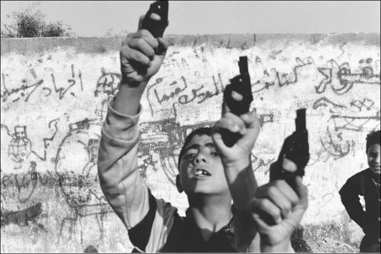 En 1993, L'Israël a fermé sa frontière avec Gaza causant une montée massive du chômage. Pourquoi ces jeunes palestiniens lèvent des jouets pistolets ?
