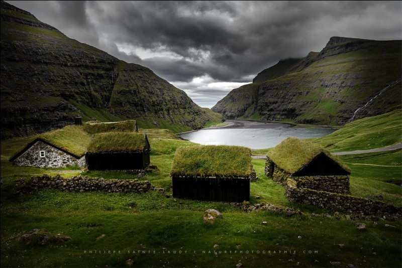 Saksun, le village que l'on voit ici, est situé dans le fond d'un fjord qui était autrefois un bras de mer, entouré de hautes montagnes. Le photographe parle de paysages Tolkien comme ces maisons typiques avec de l'herbe sur le toit. Ici, on ne sent pas le besoin de fermer sa maison à clé ou de cadenasser son vélo.En parlant de vélo, dans quel pays est-on ?