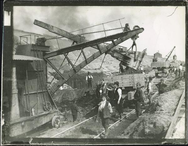 Le cliché a été pris en 1891 : on y voit les perceurs (Navvies) opérer les excavatrices de canaux à vapeur pour charger de débris les camions sur rails. Depuis le début du XIXe siècle, en Angleterre, les terrassiers ont aidé à unir le pays en creusant les canaux.Qui sont ces ouvriers qui opèrent ces engins de la ''Ruston and Proctor of Lincoln'' ?