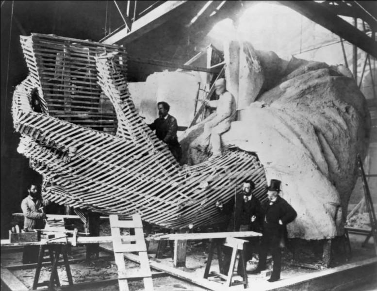 On voit ici Bartholdi expliquant le détail de la main. Il était déjà le sculpteur de la Fontaine de Bartholdi à Washington et de la Statue de Lafayette, à New York. Cette photo montre la structure en bois fabriquée à partir de liteaux utilisés pour le moulage en plâtre de la main de la statue, celle qui tient la tablette. Qu'est-ce que cela donne une fois le plâtre cassé et le bois enlevé ?