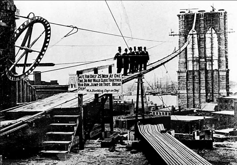En 1870, on débuta la construction. La photo date de 1877, à mi-chemin de l'ouverture : on y voit des patrons et une pancarte avec les mots '' Safe only for 25 men at the same time''. Le problème de sécurité majeur résidait dans le travail en profondeur, il n'y avait pas de paliers de décompression.Quelle est cette construction où même l'architecte Roebling est décédé d'un accident de chantier ?