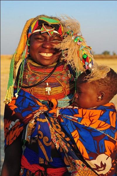 L. Gargano a capté cette mère et son fils semi-nomades de la région de Huila. Elle fait partie d'un des 1ers peuples bantous à entreprendre la migration vers le sud du continent. L'agriculture y est de subsistance et ils ont quelques poules, chèvres et bovins.Situez ces gens qui ont une façon unique d'habiller leur robe avec des ornements, portant une coiffure qui a un sens culturel important ?