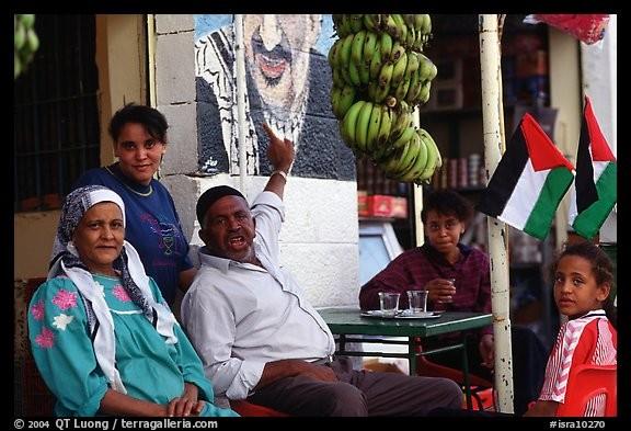Ces gens habitent un havre de paix en plein désert, dans la vallée du Jourdain en Palestine. La ville a une forte renommée pour ses sites d'histoire incomparables et aussi ses sols fertiles dont l'on voit les fruits, à côté de cette famille.D'où viennent ces Palestiniens dont le chef de famille nous pointe une murale de Yasser Arafat ?