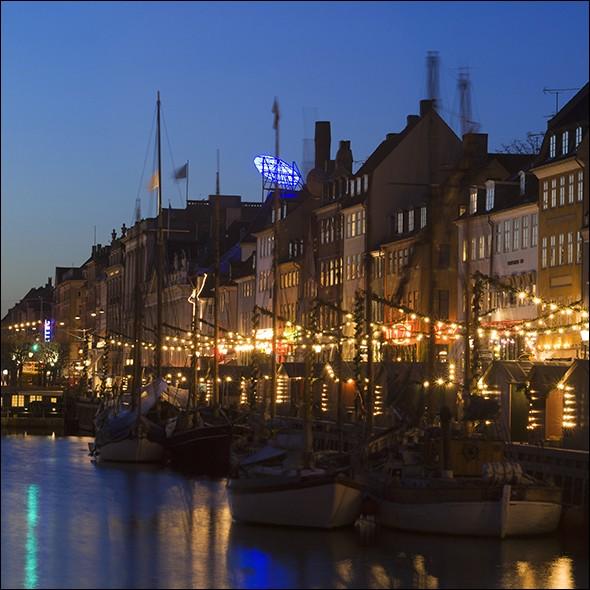 Elle a une âme la nuit avec ses lumières qui se reflètent sur l'eau. La vie nocturne n'y commence pas avant minuit et ne se termine jamais avant le lever du soleil, il y a tant à faire. Quelle est cette ville, où l'on trouve, comme sur la photo, ce parfait lieu de promenade appelé Nyhavn, jadis un repaire de marins, aujourd'hui, un quartier où trouver restaurants et bars ?