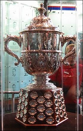Quel est ce trophée ? Il est remis actuellement à l'équipe championne de la division ouest. Son nom provient du président de la ligue de 1946 à 1977, qui fut responsable en grande partie de l'émeute de Montréal de 1955.
