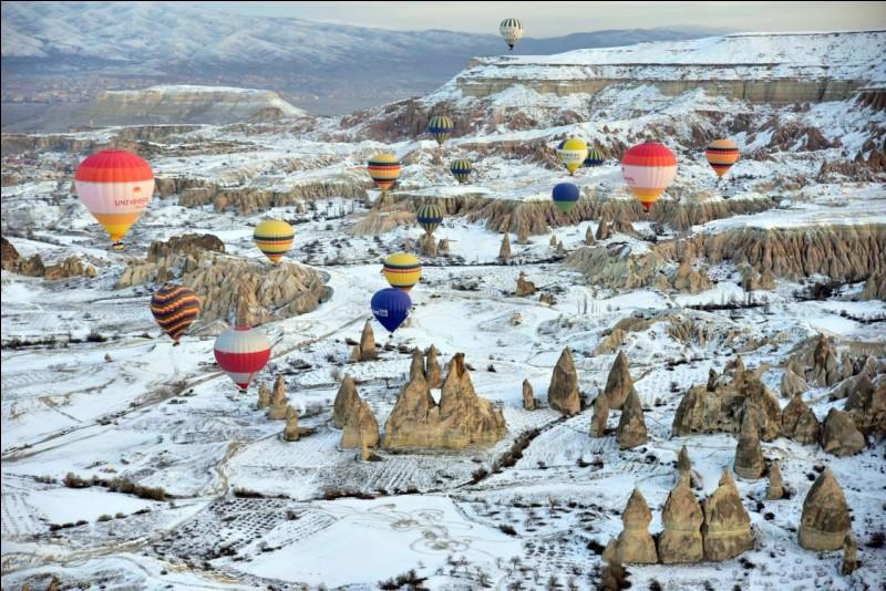 Spéciale cette photo avec la neige ! C'est quand même récent ce Festival de Mongolfière : une ''émission de Nicolas Hulot, Ushuai aurait fait sensation. Je pense que cela a relancé le tourisme dans la région'' (https://www.lecoindesvoyageurs.fr).La photo nous montre des montgolfières s'élevant au-dessus de la Cappadoce. Dans quel pays sommes-nous ?
