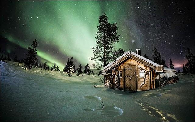Qui n'a pas rêvé pour un temps d'avoir une cabane sous la neige ? Celle-ci semble idéale pour admirer les aurores boréales. Photo proposée par Douce Cahute. Évidemment, cette maison isolée est dans un pays très nordique, mais lequel est-ce ?