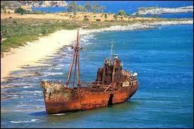 Nous voyons un navire grec célèbre pour son emplacement pittoresque sur une belle plage de sable accessible : construit au Danemark en 1950, il s' est échoué en 1981. On dit, de ce petit cargo, qu'il faisait de la contrebande entre la Turquie et l'Italie et qu'il s'est retrouvé là bien volontairement.Nommez ce site de carte postale et trouvez le nom de ce tas de tôles qui y rouille :