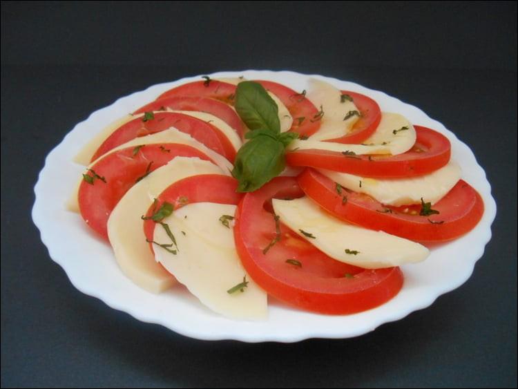 Je n'ai pas pu résister à vous servir encore ce genre d'entrée : voici une assiette de tomates mozzarella. Quelle herbe aromatique l'accompagne, et lui est indissociable ?