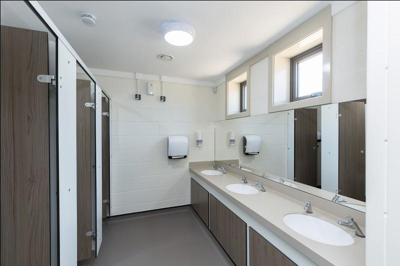 Maintenant, visitons l'extérieur. Dans un coin du bâtiment, se trouvent les toilettes. Combien de WC voyez-vous ?
