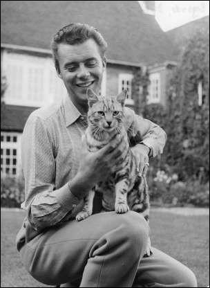 Devant sa maison, cet acteur anglais caresse son petit chat tigré (1961).Indices : acteur né en 1932 - films notables : Les Damnés - Mort à Venise - Portier de nuit
