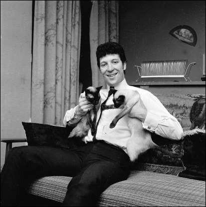 Ce chanteur pose fièrement avec ses deux chats siamois dans chaque bras (1965). Indices : chanteur né en 1940 - titres notables : She's A Lady - It's Not Unusual - Sex bomb