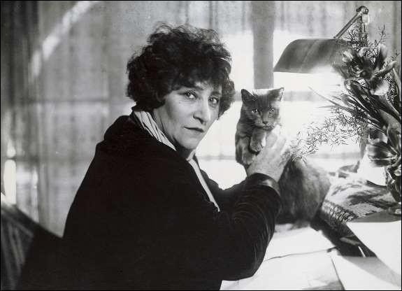 Cette célèbre femme de lettres française et son chat à ses côtés, sur son bureau d'écriture (1955). Indices : romancière née en 1830 - livres notables : Gigi - Le Blé en herbe - La Vagabonde