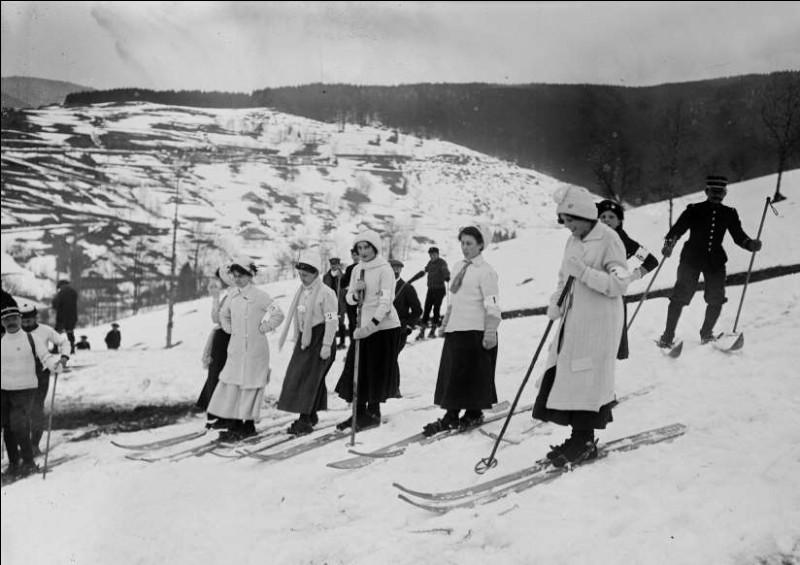 Le document date de février 1910 et on y voit des femmes qui participent à une compétition de ski. Avec leur longue jupe, cela ne sera pas facile. Elles étaient bien avant leur époque et les véritables compétitions de ski (FIS) débutèrent des décennies plus tard.Trouvez cette station qui attira les premiers skieurs, patineurs sur leur lac gelé : la station devint vite un rendez-vous mondain.
