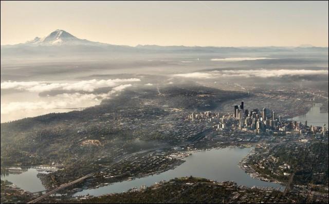 La « cité émeraude » tire son surnom des forêts verdoyantes et des collines qui forment un écrin autour d'elle. Elle n'est située que 155 km au sud du Canada et c'est un port très important pour le commerce transpacifique.Quelle est la ville que l'on trouve entre le Puget Sound, sorte d'avancée dans les terres de l'océan Pacifique et le lac Washington, avec à l'ouest, la chaîne des Olympic ?