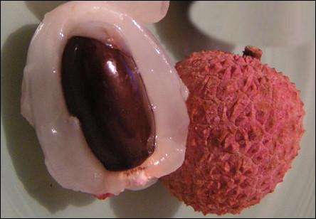 Quel est ce fruit tropical sphérique à la peau coriace d'aspect écailleux qui entoure une pulpe blanche savoureuse avec un noyau ?