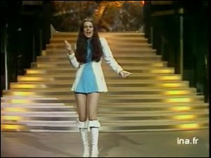 """1975 > Au printemps, une greluche* de 16 ans déguisée en majorette nous serine - avec le concours du producteur de [qui donc ?] Claude Carrère - d'un refrain """"Pas besoin ... ..."""" . Comment s'appelait-elle, déjà ?"""