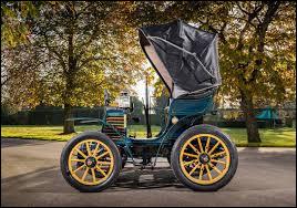 """Par quelle firme cette """"calèche"""" munie d'un moteur arrière à deux cylindres, avec transmission à chaîne fut-elle produite, en 1899 (C'était la première automobile de cette marque) ?"""