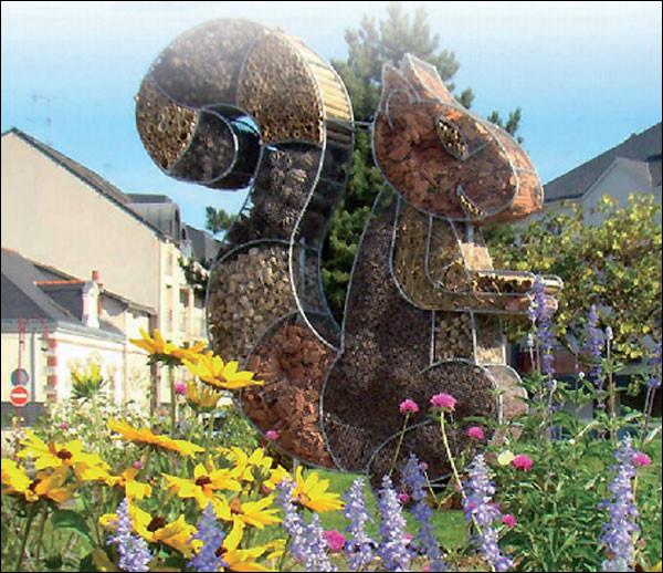 Jolie sculpture dans un jardin fleuri ! C'est...Vous pouvez agrandir l'image.