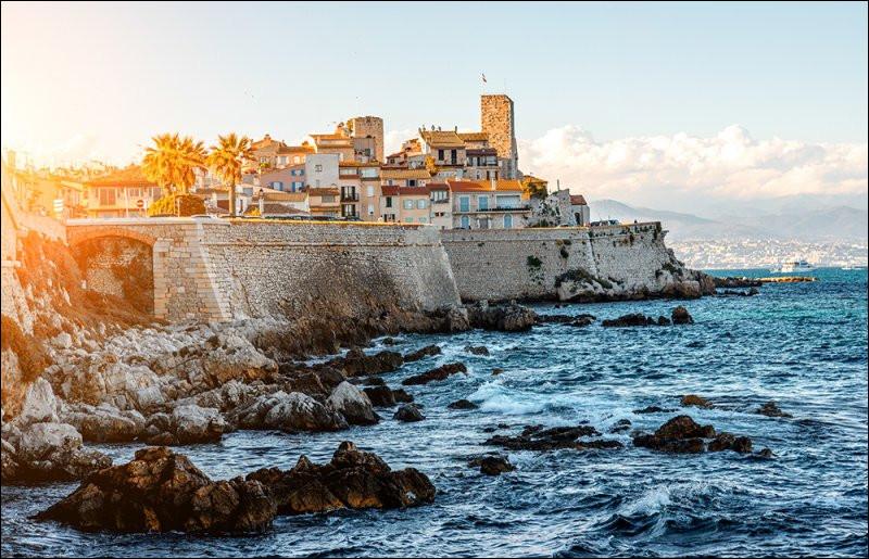 """Comment oublier ce paysage des Alpes enneigées vu du port de cette vieille ville entourée de remparts du XVIe siècle. Je me souviens du fort Carré, du marché incontournable, et d'un petit restaurant qui se nommait """"La Côte à l'os"""". Quelle est cette ville des Alpes-Maritimes située entre Nice et Cannes ?"""