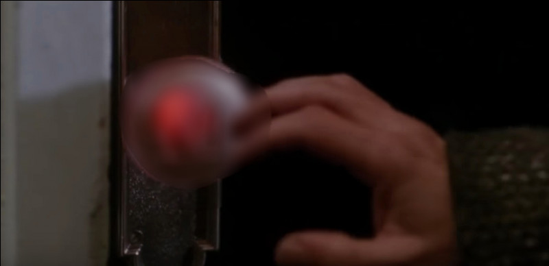 Quelle lettre se retrouve sur la main du cambrioleur Harry après qu'il se soit brûlé sur la poignée de porte ?