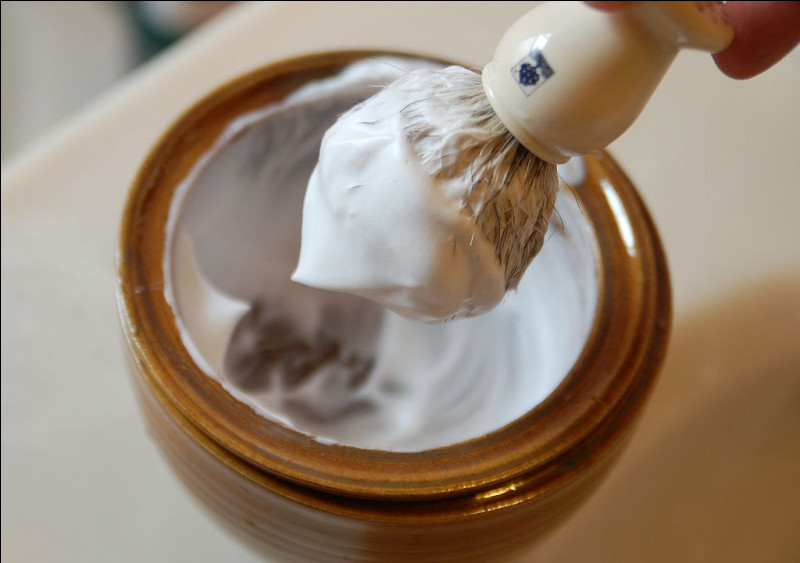 Quel est le nom de cette brosse utilisée pour appliquer du savon à barbe sur un visage avant de le raser ?