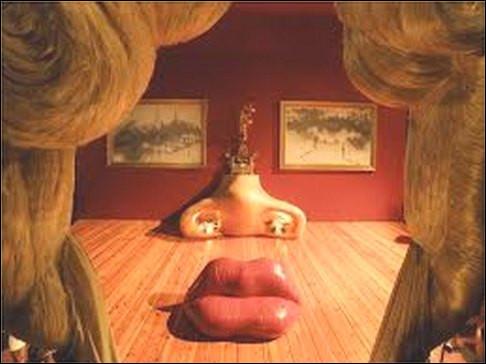 """Cette œuvre surréaliste du """"Visage de Mae West"""" est en réalité composé d'un canapé rouge, d'une cheminée et deux tableaux au mur. Qui a produit cette installation ludique ?"""