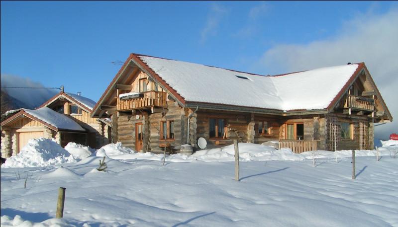 Maison en rondins de bois brut empilés, ajustés et entrecroisés aux angles.