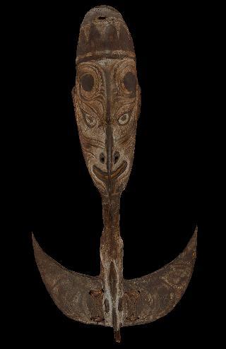 7. En bois, ce crochet sculpté d'un visage présentant des motifs en volutes est utilisé en temps de guerre. Il est caractéristique de la façon de faire :