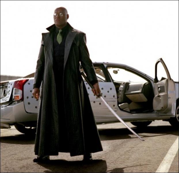 Dans quel film de la saga 'Matrix' voit-on Laurence Fishburne devant une voiture de police criblée d'impacts de balles après une course-poursuite mémorable sur une autoroute ?
