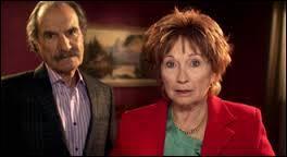De quelle commerçante Raymond dit-il être amoureux, juste pour rendre Huguette jalouse ?