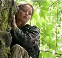 Traquée par un groupe de poursuivants, Katniss se réfugie en haut d'un arbre. De quelle manière arrive-t-elle à faire fuir la bande de tueurs ?