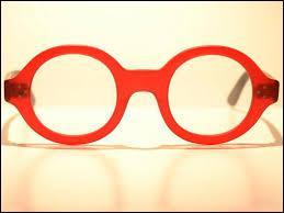 Qui porte des lunettes de vue rouges aux verres très épais ?