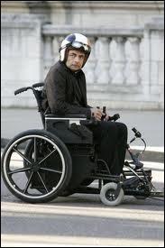Quand Johnny veut prendre l'ascenseur pour un fauteuil roulant, quel objet sort-il pour monter en premier ?