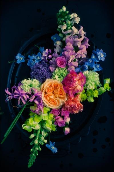 Présentées à plat, dans une coupe, ce mélange de fleurs est très coloré. Quelles sont ces fleurs en grappes, qu'on voit en haut et en bas de la photo ?