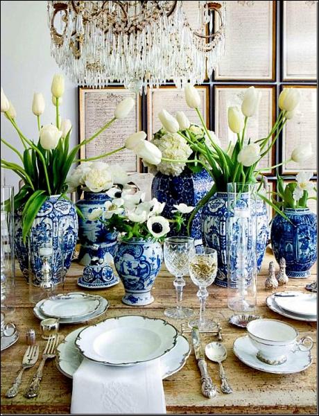 Ce très bel arrangement doit beaucoup à des vases bleus et blancs, qui accueillent des fleurs blanches. Quelles sont les fleurs placées au milieu de la photo, entre les bouquets de tulipes ?