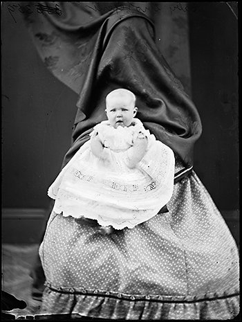 Sur cette photographie comme sur d'autres de la même époque, la femme qui tient l'enfant est recouverte d'un drap ou d'une nappe. Pourquoi ?